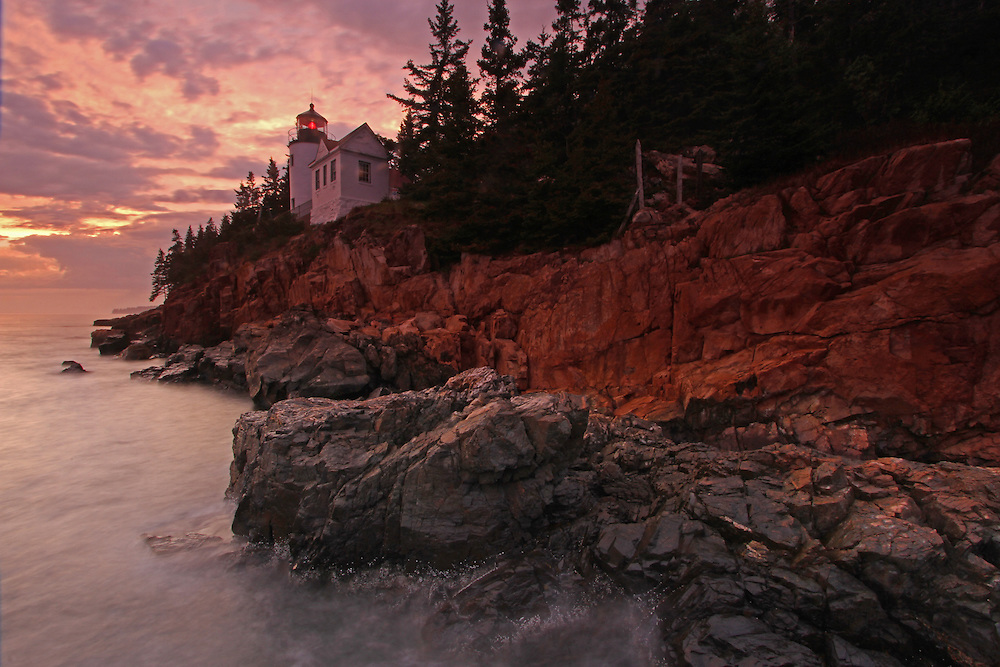 Bass Harbor Lighthouse photography fine art prints are available as museum quality photography prints, canvas prints, acrylic prints or metal prints. Prints may be framed and matted to the individual liking and room decor needs:<br /> <br /> http://juergen-roth.artistwebsites.com/featured/sunset-at-bass-harbor-head-lighthouse-juergen-roth.html<br /> <br /> Bass Harbor Head Lighthouse is a scenic New England lighthouse located at the southeast corner of Mount Desert Island within Maine Acadia National Park. The picturesque lighthouse towers over the swirling Atlantic Ocean and granite seacoast, marking the gateway to Bass Harbor and Blue Hill Bay. It is one of the most iconic scenery of Acadia NP as Bass Harbor Head Light is dramatically located on the edge of rugged cliffs.<br /> <br /> The history of Bass Harbor Head Light started in 1855 when it was deemed that there was sufficient reason for a lighthouse at the mouth of Bass Harbor. $5000 was appropriated by Congress for its construction in 1858. The construction of a fog bell and tower, which no longer remains today, was completed in 1876 with a much larger 4000 pound (1800 kg) bell being placed inside the tower in 1898. The keeper's house remains in its original configuration with the exception of a 10-foot addition that was added in 1900. The lighthouse was added to the National Register of Historic Places as Bass Harbor Head Light Station on January 21, 1988. In 1902, an oil storage house constructed of brick was built 205 feet northwest of the lighthouse. Bass Harbor's fifth order Fresnel lens was replaced in 1902 with a larger fourth order. This lens was manufactured by the French company Henry-Lepaute. This lens remains in service today.<br /> <br /> Good light and happy photo making!<br /> <br /> My best, <br /> <br /> Juergen <br /> www.RothGalleries.com <br /> www.ExploringTheLight.com <br /> http://whereintheworldisjuergen.blogspot.com <br /> @NatureFineArt <br /> https://www.facebook.com/naturefineart