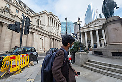 © Licensed to London News Pictures. 17/03/2020. London, UK. A man wearing a face mask walks through the Bank area in the City of London as the Coronavirus outbreak spreads. Photo credit: Ray Tang/LNP