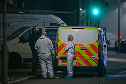 © Licensed to London News Pictures. 11/11/2020. Slough, UK. Forensic investigators stand next to a police vehicle on Stoke Poges Lane. A person was reportedly stabbed in Slough on Tuesday 10/11/2020. A large cordon was put in place by Thames Valley Police centred around shops on Stoke Poges Lane and included a large section of Bradley Road. Photo credit: Peter Manning/LNP
