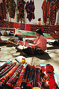 Indian woman weaving with a backstrap loom in Oaxaca, Mexico.