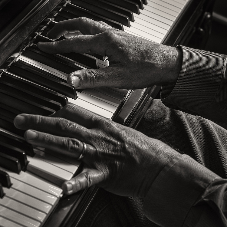 John Bizianes playing the piano in his studio.