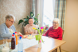 Girl playing board game with senior women in rest home