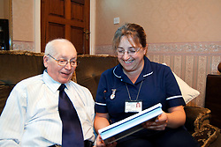 Discharged elderly patient is visited in his home by district nurse Bradford Yorkshire UK