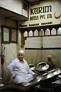 Salahuddin one of the directors at Karim's Restaurant serves food from pots. Delhi, India Delhi, India<br /> Karim's is a Delhi landmark was started by Haji Karimuddin who decided to open a restuarant catering to people coming to Delhi for the Coronation Durbar in 1911