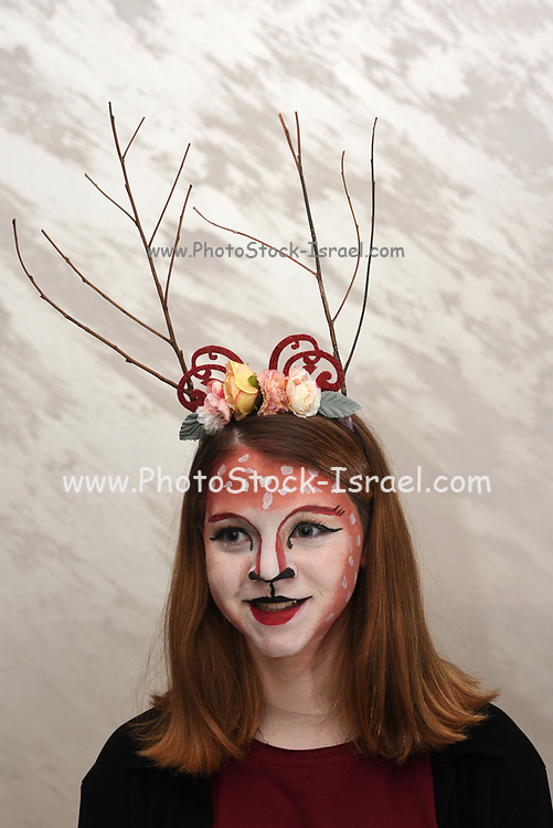 Young teen girl with body paint and costume dressed up as a forest fairy ready for a Halloween party