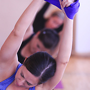 Amy Barrows, front, Shelley Jackson, center, and Beth Mendenhall participate in an Aerial Yoga class at Salty Dog Yoga Sunday April 6, 2014 in Carolina Beach, N.C. (Jason A. Frizzelle)