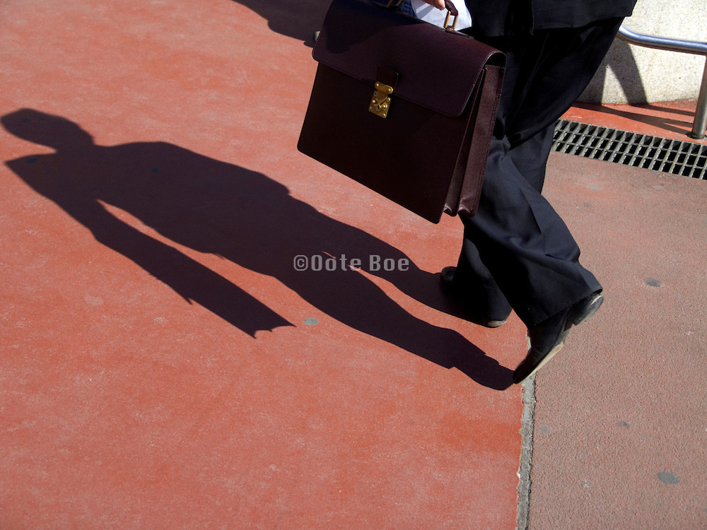 Silhouette of a man holding a briefcase in motion