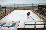 Havana, Cuba. July 2015. A boy wiping a skating rink during a summer afternoon. The rink was made up of plastic sheets.