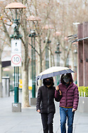 A couple wearing sunglasses and facemasks huddle under an umbrella as they brave the Melbourne weather during COVID-19 in Melbourne, Australia. Hotel quarantine linked to 99% of Victoria's COVID-19 cases, inquiry told. This comes amid a further 222 new cases being discovered along with 17 deaths. Melbourne continues to reel under Stage 4 restrictions with speculation that it will be extended. (Photo by Dave Hewison/Speed Media)