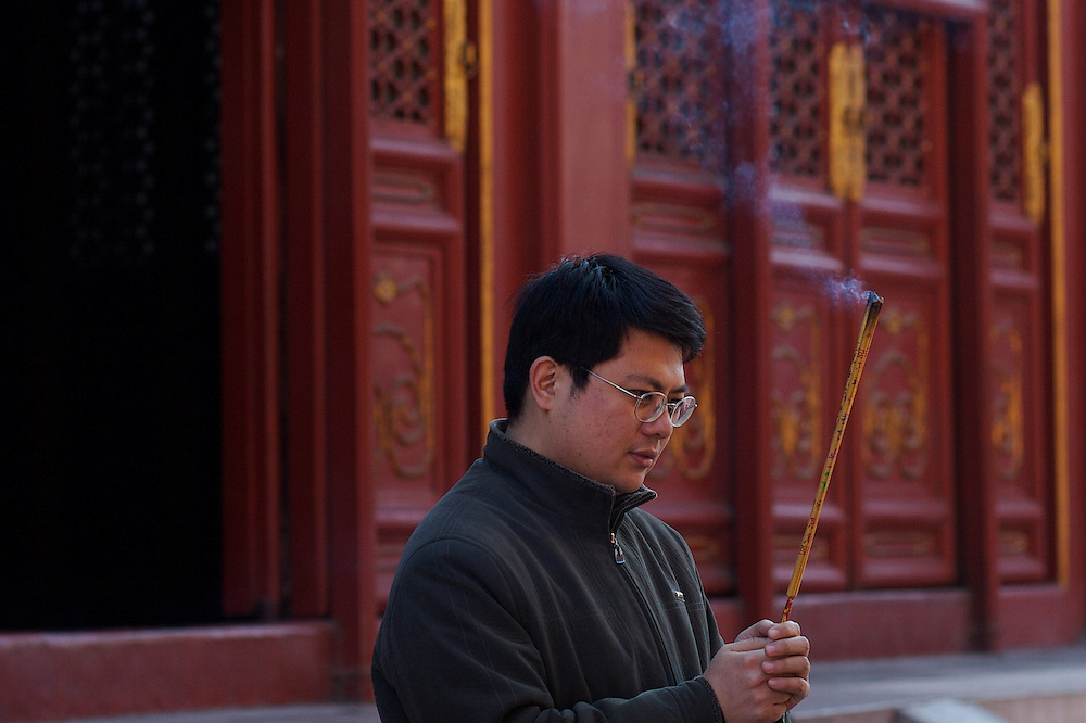 In the fifth courtyard at Yonghegong a man burns several sticks of incense. This Tibetan Temple is known to tourists as Lama Temple and it's located in Dongcheng District Beijing, China. This is the largest Temple of its kind outside of Tibet.  In 1723 the structure was turned into a Temple after the resident became the third Qing Emperor.