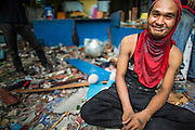 """12 DECEMBER 2012 - BANGKOK, THAILAND: A demolition worker relaxes at the end of his shift at """"Washington Square"""" a notorious entertainment district off Sukhumvit Soi 22 in Bangkok. Demolition workers on many projects in Thailand live on their job site tearing down the building and recycling what can recycled as they do so until the site is no longer inhabitable. They sleep on the floors in the buildings or sometimes in tents, cooking on gas or charcoal stoves working from morning till dark. Sometimes families live and work together, other times just men. Washington Square was one of Bangkok's oldest red light districts. It was closed early 2012 and is being torn down to make way for redevelopment.    PHOTO BY JACK KURTZ"""