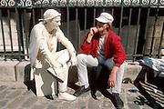 FRANCE, PARIS, MONTMARTRE A mime artist and a house painter share a smoke outside the Basilique du Sacre-Coeur