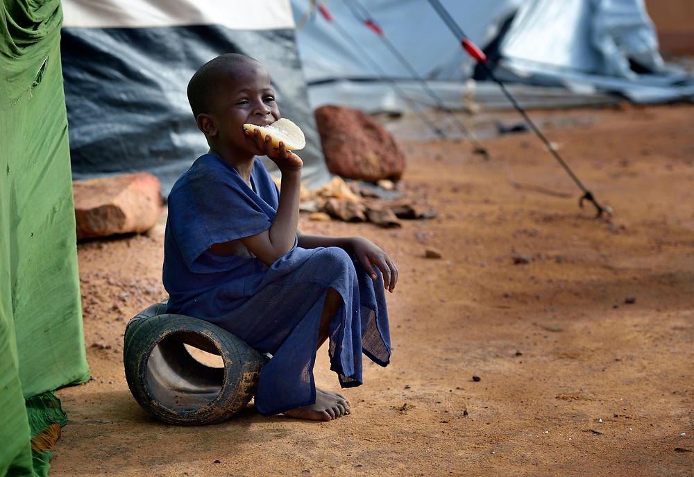 A boy eats bread in a camp in Mopti, Mali, for families displaced by the fighting in the north of the country. Islamist rebels seized control of the north of Mali in 2012, but were chased out in early 2013 by French troops. Many displaced and refugee families have yet to return, preferring to wait for better security and improved economic conditions in the north.