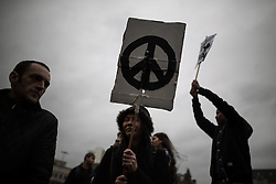 """© Licensed to London News Pictures . 05/12/2015 . Manchester , UK . A woman holds a placard with the CND logo . Approximately one hundred anti-war protesters march through central Manchester against Parliament's decision to vote in favour of bombing against """" ISIS """" , in Syria . Photo credit : Joel Goodman/LNP"""