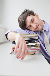 Businessman sleeping on stack of files in office