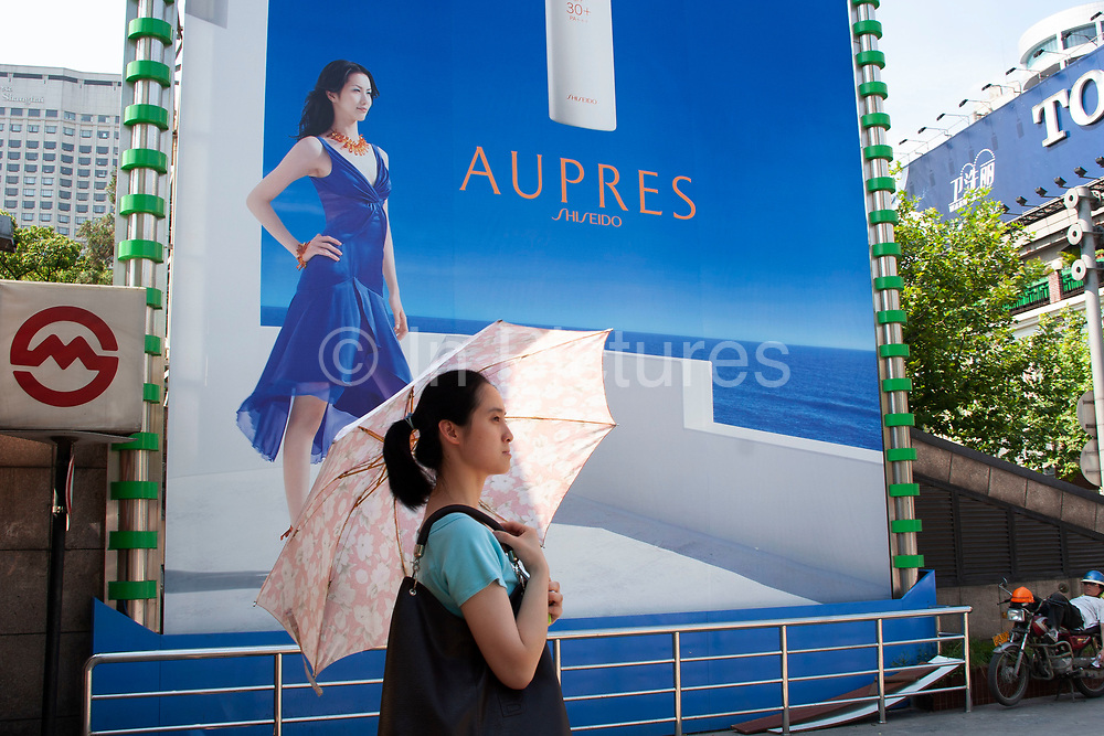 A young Chinese woman exits Huai Hai Road, Huai Hai Lu, Metro station underneath a giant advertising hoarding on Huai Hai Road, in downtown Shanghai, China. This exit is right in the centre of Shanghai's main shopping street where many western stores have their first Chinese branches and where the young and beautiful can be seen carrying seemingly endless bags of shopping. Advertising, like this huge one for Aupres, lines this street in particular. Image is very important to younger Chinese. After so many years of no options, westernization has opened up their fashion possibilities and choices. This woman is shielding herself from the sun with an umbrella in an attempt which many women use to keep their skin white.