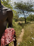Sharing gazelle meat with the neighbor. At the Hadza camp of Senkele.