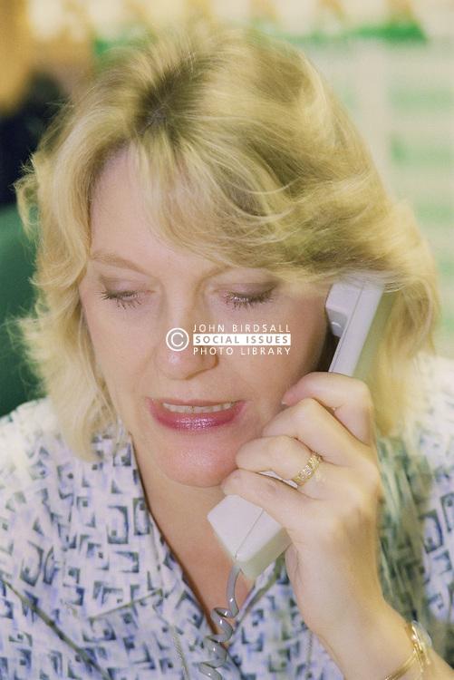 Female receptionist using telephone at Maternity reception desk,