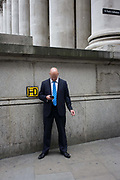 Pinstriped suit businessman checks messages during a cigar break, beneath tall of columns at Cornhill, City of London. Holding his smartphone in one hand, and a small cigar in the other, the gentleman stands in a bold, confident pose, wearing a pinstriped suit and blue striped tie, the top of his bald head shown to us as he looks down to view the screen. A fire hydrant number code is on the wall at his elbow, the columns of the Cornhill Exchange above plus a sign pointing to the nearby St Paul's Cathedral. The City is a major business and financial centre. Throughout the 19th century, the City was perhaps the world's primary business centre, and it continues to be a major meeting point for businesses