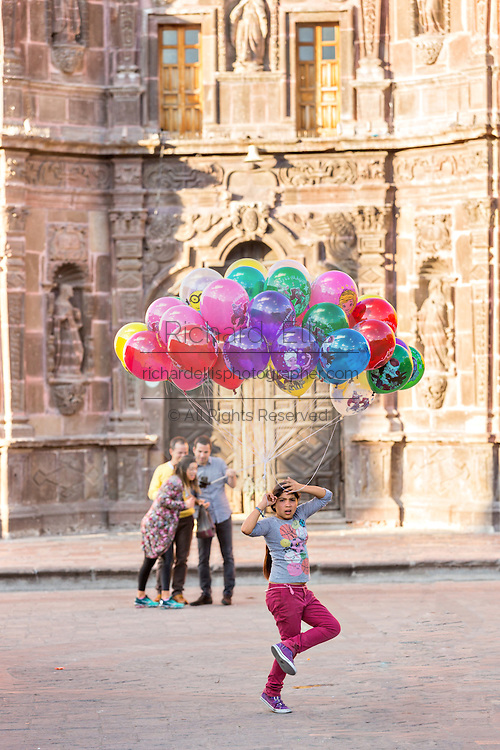 A young girl sells balloons in the Plaza de la Soledad by the Nuestra Señora de la Salud Church in the historic center of San Miguel de Allende, Mexico.