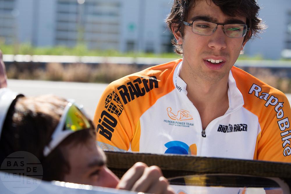 Sebastiaan Bowier overlegt na afloop van de testrondes met George-Emile over het luchtmasker. Het Human Power Team Delft en Amsterdam, bestaande uit studenten van de TU Delft en de VU Amsterdam, trainen op de RDW baan in Lelystad voor de laatste keer voor de recordpoging. In september wil het team met Jan Bos en Sebastiaan Bowier het snelheidsrecord op de fiets te verbreken. Dat record staat nu op 133 km/h.<br /> <br /> Sebastiaan Bowier is giving comments on the air mask to George-Emile. Human Power Team Delft and Amsterdam are having the last training for the record attempt in Battle Mountain (USA) at the RDW test track in Lelystad. The team will try to break the world speed record with a human powered vehicle with riders Jan Bos and Sebastiaan Bowier. The record is now at 133 km/h..
