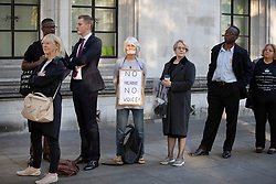 © Licensed to London News Pictures. 17/09/2019. London, UK. A protestor stands amongst people lining up outside The Supreme Court. Today the court will start hearing appeals against Scottish and English courts decisions on the government's proroguing of Parliament. Photo credit: Peter Macdiarmid/LNP