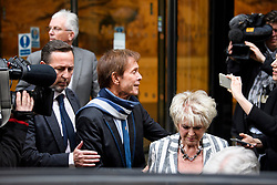 © Licensed to London News Pictures. 13/04/2018. London, UK. SIR CLIFF RICHARD leaves the Rolls Building of the High Court in London with television presenter GLORIA HUNNIFORD after giving evidence is a case where he is claiming damages against the BBC for loss of earnings. The 77-year-old singer is suing the corporation after his home in Sunningdale, Berkshire was raided following allegations of sexual assault made to Metropolitan Police. Photo credit: Ben Cawthra/LNP