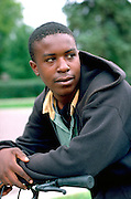 African American teen age 18 deep in thought leaning on bicycle.  St Paul Minnesota USA