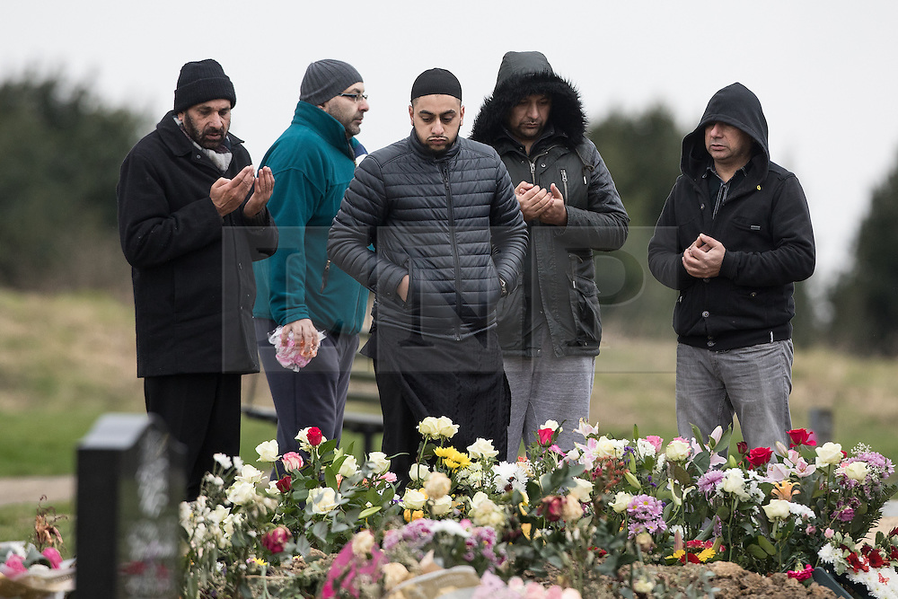 © Licensed to London News Pictures. 06/01/2017. Huddersfield, UK. People stand around the grave at the funeral of Yassar Yaqub at Hey Lane Cemmetary in Huddersfield, West Yorkshire. Yaqub, 28, from Huddersfield, was shot dead in a car stopped near junction 24 of the M62 as part of a planned police operation. Photo credit: Joel Goodman/LNP