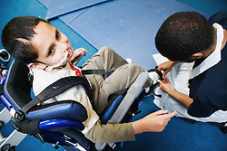 Child with physical disability in supportive seat,