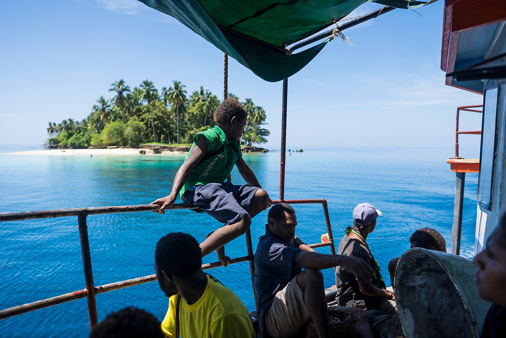 Passengers aboard the M.V. Thomson, a small cargo and passenger vessel that connects Madang and Karkar Island in Papua New Guinea, sail past a small island shortly after departing Madang.<br /> <br /> (August 8, 2017)