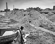 Woman sunbathing in the middle of construction yard