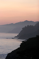 4 August 2006: Scenic view looking North along Highway 1 at sunset through central California along the coast of Big Sur.  Blue sky, surf, yellow weeds and rolling hills.