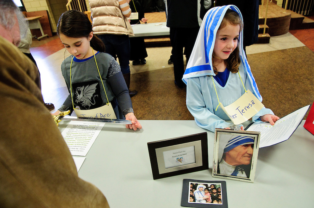 """Second grader Kate Harring (R) portrays Mother Teresa while classmate Emily Walter embodies Joan of Arc for attendees of the annual Parade of Saints at St. Michael School in Orland Park, February 2. During the event, costumed students stand motionless in the school commons for parents, grandparents and friends to """"activate"""" the Saint, who will offer a brief historical description. The session is followed by a parade through the school. l Brian J. Morowczynski~ViaPhotos..For use in a single edition of Catholic New World Publications, Archdiocese of Chicago. Further use and/or distribution may be negotiated separately. ..Contact ViaPhotos at 708-602-0449 or email brian@viaphotos.com."""