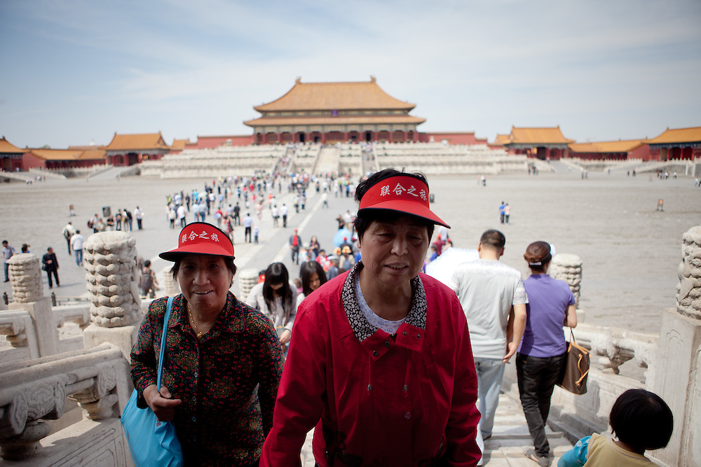 """Members of a Chinese tourist group inside  """"The Forbidden City"""" which was the Chinese imperial palace from the Ming Dynasty to the end of the Qing Dynasty. It is located in the middle of Beijing, China. Beijing is the capital of the People's Republic of China and one of the most populous cities in the world with a population of 19,612,368 as of 2010."""