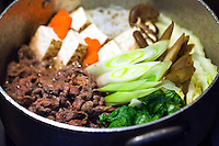 Sukiyaki is a Japanese dish cooked in the nabemono Japanese Hot pot style. It consists of thinly sliced beef slowly simmered at the table, with vegetables and other ingredients in a shallow iron pot in a mixture of soy sauce, sugar, and mirin. Before being eaten, the ingredients are usually dipped in a small bowl of raw, beaten eggs.