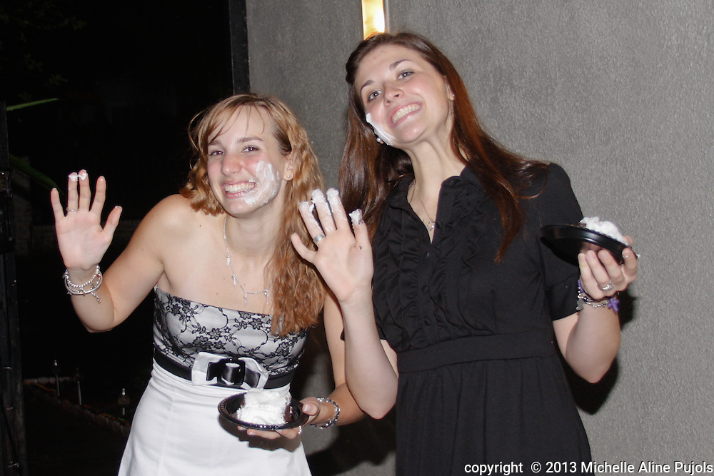 Two girls with cake on their faces.