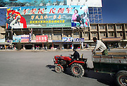 """A tractor passes a propaganda billboard depicting the People's Liberation Army on one side and smiling Tibetans on the other, reading """"The army loves the people"""" in Shangri-La, meant to quell tensions between Tibetans and Han Chinese."""
