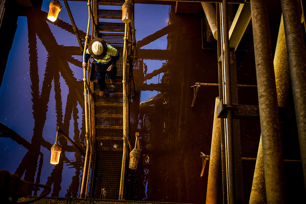 Workers move down stairs at a processing plant in the Pilbara region of Western Australia.