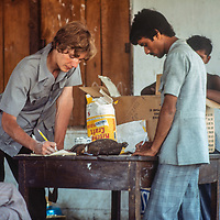 An aid worker prepare to distribute food at Mirpur Destitute Camp, set up at an abndoned soap factory near Dhaka, Bangladesh,  after a cyclone & bloody war of independence left millions of peole homeless.  1977 image.