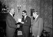 """17/07/1967<br /> 07/17/1967<br /> 17 July 1967<br /> """"Silver Bear"""" award presentation at Iveagh House by Mr. Aiken to Mr. Louis Marcus. The award was won by the film Fleá Cheoil at the Berlin International Film Festival, directed by Louis Marcus. Image shows (l-r): An Tánaiste Frank Aiken presenting the """"Silver Bear"""" to Mr. Louis Marcus. Dr. Heinz Trutzschler von Falkenstein, Ambassador of the Federal Republic of Germany on right."""