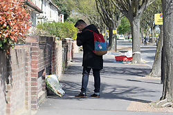 © Licensed to London News Pictures. 17/04/2018. London, UK. Neighbour, Said Bhueloo who was with the victim lays flowers at the crime scene cordon at Chestnut Avenue in Forest Gate, east London where a teenager was fatally stabbed last night. Police were called to the stabbing in Chestnut Avenue at around 22:50 on Monday 16th April and attended along with London Ambulance Services and paramedics from London's Air Ambulance. The victim, believed to be an 18 year old man was pronounced dead at the scene. This is the 60th killing of the year so far in London.. Photo credit: Vickie Flores/LNP