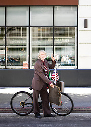 Senior Man with Bicycle Making Peace Sign