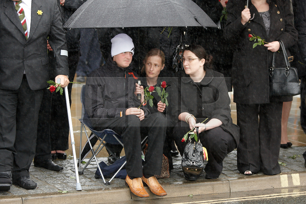 © Licensed to London News Pictures.  07/06/2012.CARTERTON, UK. Family, friends and colleagues pay their respects during very heavy rain at the repatriation ceremony for Cpl Michael John Thacker, from 1st Battalion, The Royal Welsh and Pivate Gregg Thomas Stone from 3rd Battalion, the Yorkshire Regiment. Photo credit :  Cliff Hide/LNP