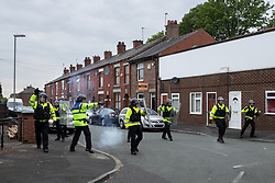© Licensed to London News Pictures . 18/05/2019. Oldham, UK. Those opposed to Yaxley-Lennon are pushed back through Oldham , away from the rally , by riot police as bangers are thrown . Former EDL leader Stephen Yaxley-Lennon (aka Tommy Robinson ) continues his campaign for a seat in the European Parliament representing the North West of England , by visiting Oldham . Photo credit: Joel Goodman/LNP
