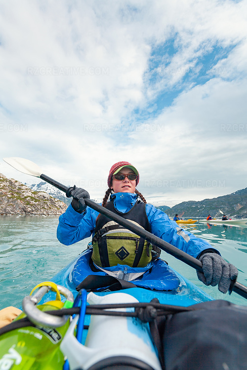 A woman paddles a sea kayak in Johns Hopkins Inlet, part of southeast Alaska's Glacier Bay National Park.