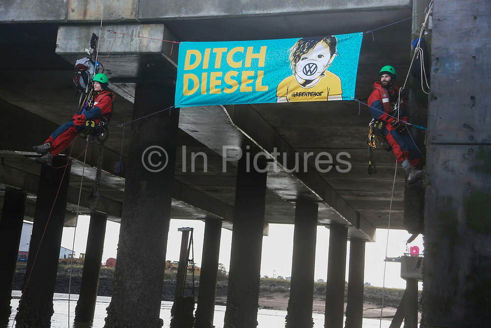 Greenpeace activists blocking the way for the cargo ship to dock September 21st 2017, Thames Estuary, Kent, United Kingdom. Greenpeace volunteers in kayaks, speed boats and climbers on the jetty prevent the 23,498-tonne cargo ship Elbe Highway from docking at Sheerness in Kent.  The cargo ship is bringing Volkswagen diesel cars into the UK and the Greenpeace action is to prevent this from happening and to make VW ditch diesel. Two climbers board the ship and hang a banner on the roll-on roll-off part of the ship preventing any cars from being off-loaded. The action is part of a long running Greenpeace campaign to curb diesel emmissions and air pollution broght on by diesel cars.