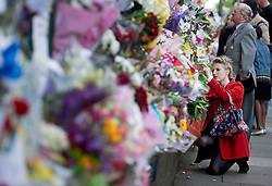 © London News Pictures. 25/05/2013. Woolwich, UK. A woman laying flowers at the scene where Drummer Lee Rigby was murdered by two men in Woolwich town centre in what is being described as a terrorist attack. Photo credit: Ben Cawthra/LNP