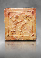 6th-7th Century Eastern Roman Byzantine  Christian Terracotta tiles depicting Abraham about to offer his son Isaac as a sacrifice<br />   - Produced in Byzacena -  present day Tunisia. <br /> <br /> These early Christian terracotta tiles were mass produced thanks to moulds. Their quadrangular, square or rectangular shape as well as the standardised sizes in use in the different regions were determined by their architectonic function and were designed to facilitate their assembly according to various combinations to decorate large flat surfaces of walls or ceilings. <br /> <br /> Byzacena stood out for its use of biblical and hagiographic themes and a richer variety of animals, birds and roses. Some deer and lions were obviously inspired from Zeugitana prototypes attesting to the pre-existence of this province's production with respect to that of Byzacena. The rules governing this art are similar to those that applied to late Roman and Christian art with, in the case of Byzacena, an obvious popular connotation. Its distinguishing features are flatness, a predilection for symmetrical compositions, frontal and lateral representations, the absence of tridimensional attitudes and the naivety of some details (large eyes, pointed chins). Mass production enabled this type of decoration to be widely used at little cost and it played a role as ideograms and for teaching catechism through pictures. Painting, now often faded, enhanced motifs in relief or enriched them with additional details to break their repetitive monotony.<br /> <br /> The Bardo National Museum Tunis, Tunisia. Against a grey art background.