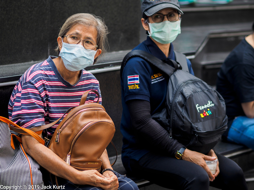 """14 JANUARY 2019 - BANGKOK, THAILAND:       Women wearing dust filters wait for a bus in Bangkok. Bangkok has been blanketed by heavily polluted air for almost a week. Monday morning, the AQI (Air Quality Index) for Bangkok  was 182, worse than New Delhi, Jakarta, or Beijing. The Saphan Kwai neighborhood of Bangkok recorded an AQI of 370 and the Lat Yao neighborhood recorded an AQI of 403. An AQI above 50 is considered unsafe. Public health officials have warned people to avoid """"unnecessary"""" outdoor activities and wear breathing masks to filter out the dust.   PHOTO BY JACK KURTZ"""